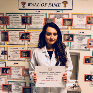 "Marjan Khan with her award in front of the Natural Sciences ""Wall of Fame"""