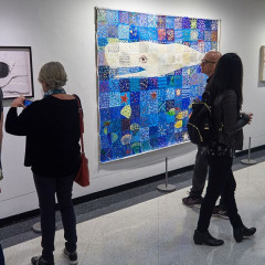 Guests examine artwork in The Moby-Dick Project exhibition