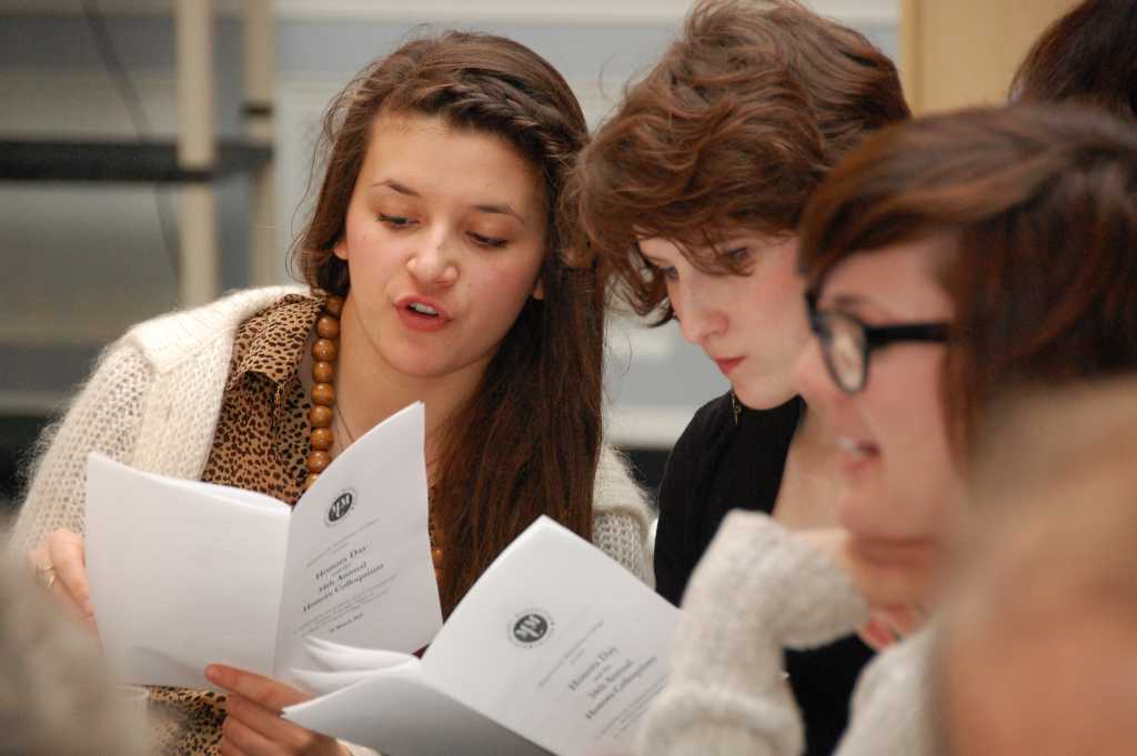 Students review the program for Honors Day